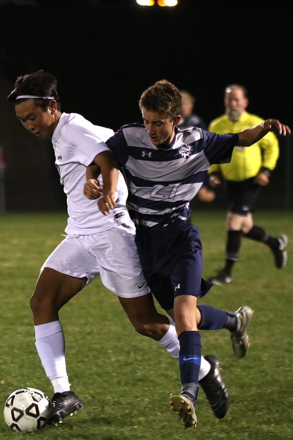 Battling for the ball, freshman Dylan Ashford goes up against an opponent.