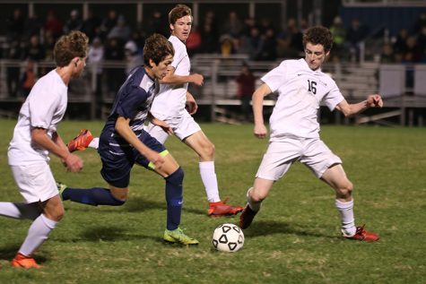 Dribbling by his opponents, sophomore Yahel Anderson heads towards the goal. The boys soccer team lost 1-0 in overtime on Tuesday, Oct. 22 against Blue Valley.