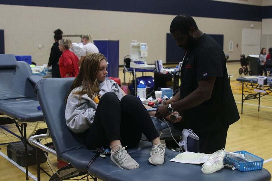 As the first person to give blood, senior Kylie Conner senior lies on the table waiting to finish her donation.