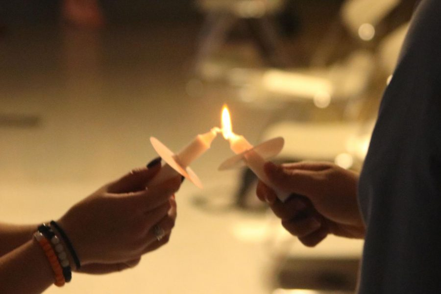 Lighting their candles, members and soon to be members pass around a flame.