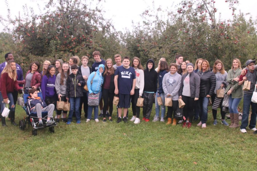 The class of Peers in Learning students enjoy their time at the apple orchard.