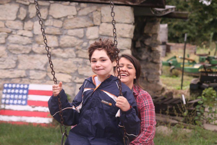 At the apple orchard, senior Rachel Sunderman helps push junior Charlie Peterson on the swing.