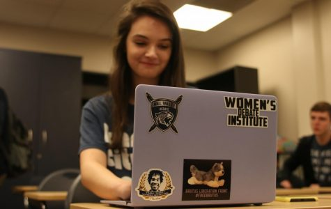 Using software designated for debate, sophomore Taylor Doyle types on her personal laptop that she customized with a #FreeBrutus sticker.