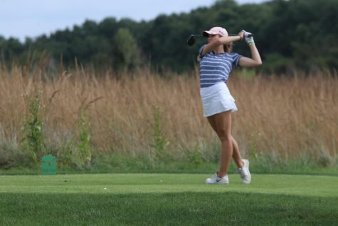 Watching the ball, junior Caroline Lawson finishes her swing at Eagle Bend Golf Course on Wednesday, Oct. 2nd.