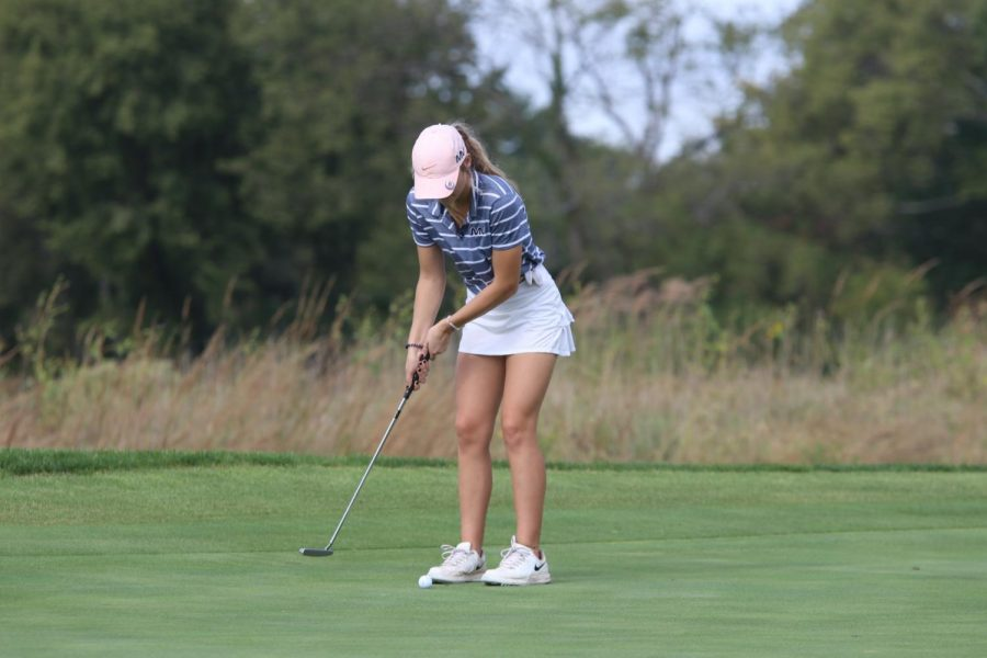 Gripping the club, junior Caroline Lawson putts the ball.