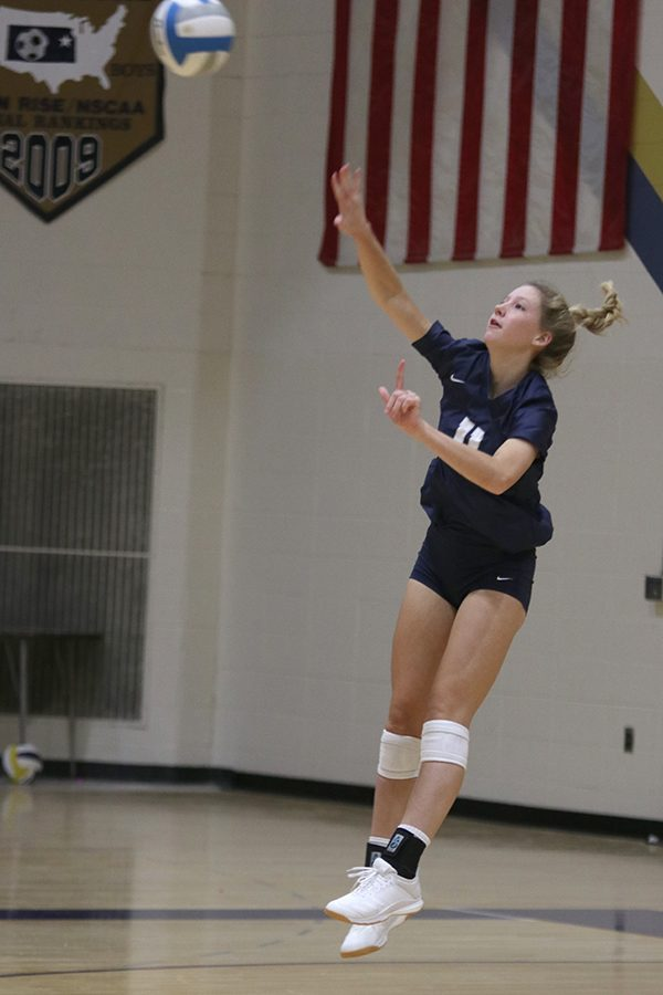 Extending her arm, sophomore Kate Roth follows through to finish the serve to Aquinas.