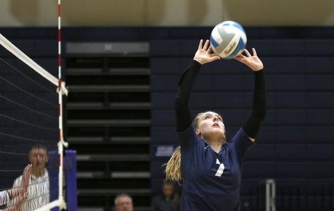 Extending her arms, sophomore Sydney Fiatte uses her fingers to set the ball to her teammate. The team competed in a triangular at St. Thomas Aquinas against Aquinas and Bishop Miege on Tuesday, Oct. 15. They beat Miege 2-0 but lost to Aquinas 0-2.