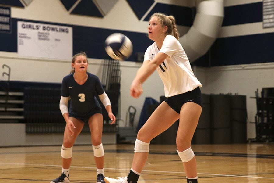Hitting the volleyball, sophomore Kate Roth uses force to ensure that the ball makes it over the net.