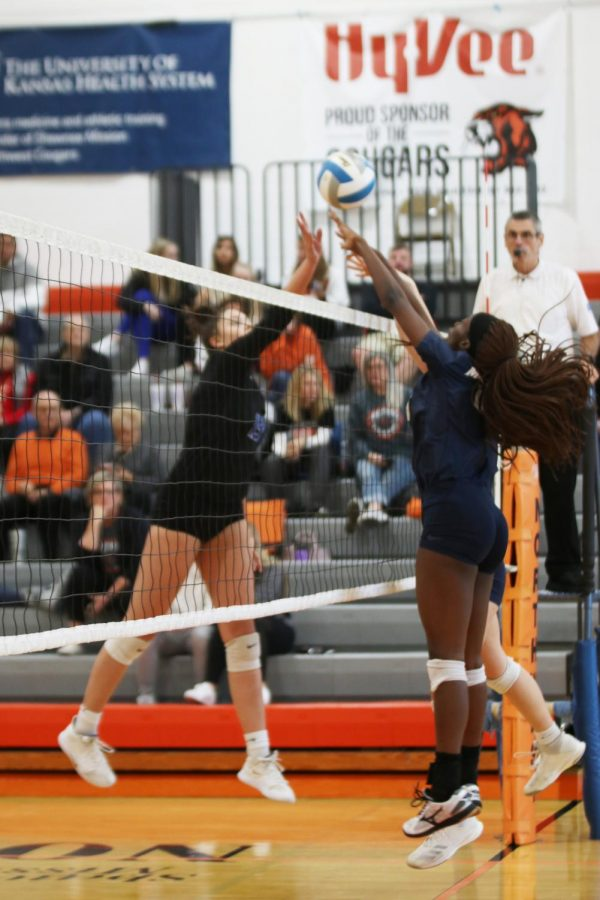 Awaiting the ball being tipped over the net, senior Faith Archibong jumps in the air and extends her arms, ready to block.
