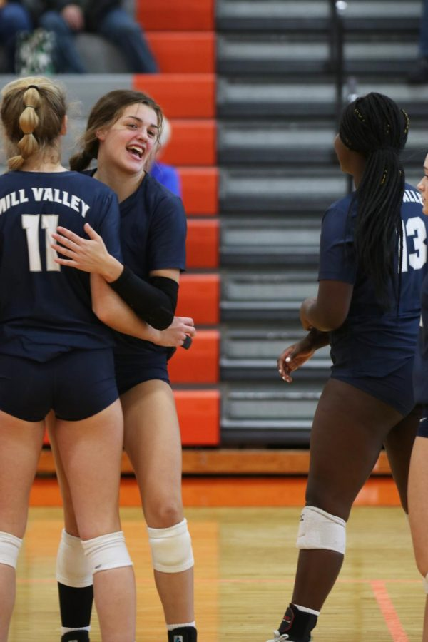 After scoring a point, junior Molly Carr celebrates with her teammate at the net.