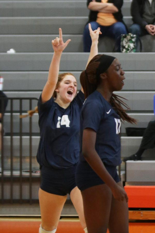 After scoring a critical point, the Jags take the lead in the third set against Olathe Northwest. In celebration, sophomore Brylee Peterson raises her arms in the air and cheers in celebration with senior Faith Archibong.