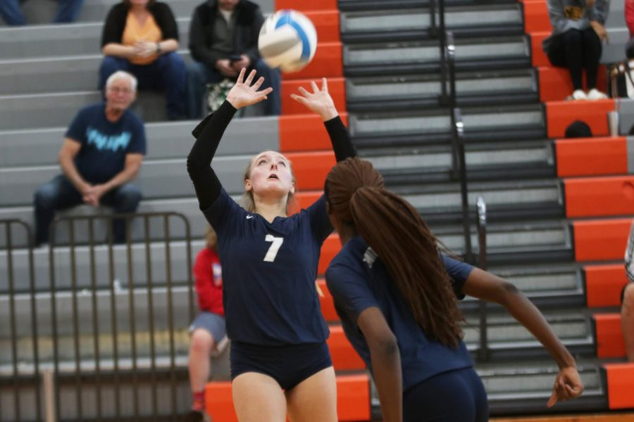 Arms raised above her head, sophomore Sydney Fiatte sets the ball for a teammate.