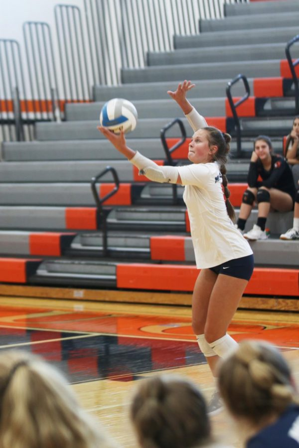 With her focus on the ball, junior Jaden Ravnsborg prepares to serve.
