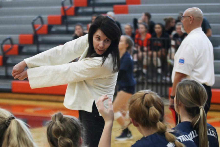 Communicating with a player, coach Debbie Fay demonstrates how a ball was hit.