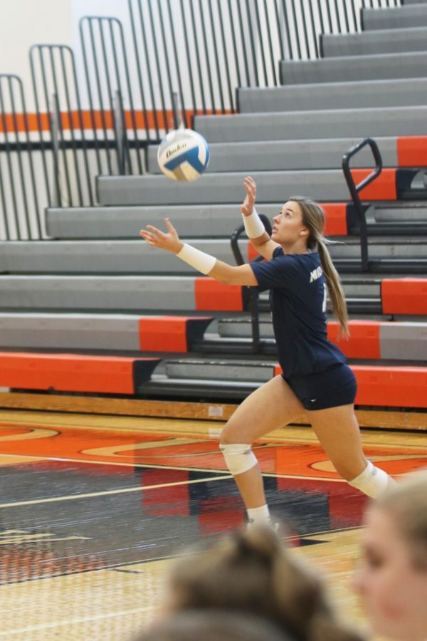 After tossing the ball in the air, senior Emma Fox prepares to serve it over the net.