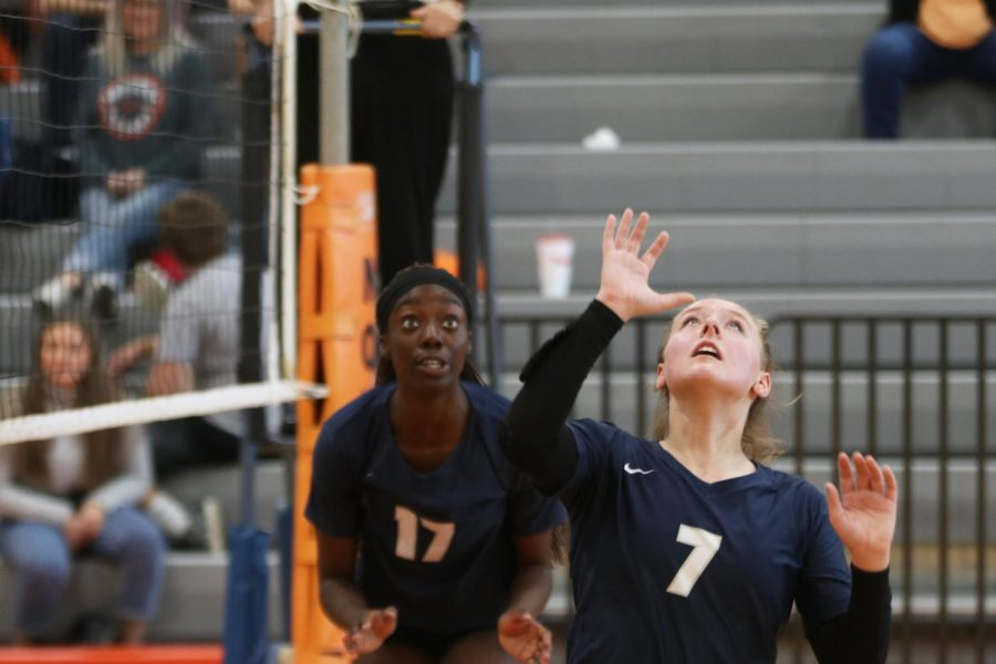 Looking up, sophomore Sydney Fiatte prepares to set the ball for her teammate while senior Faith Archibong watches from behind her.