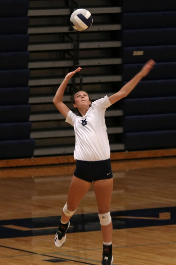 About to serve the ball, sophomore Amara Traiger extends her arm above her head.