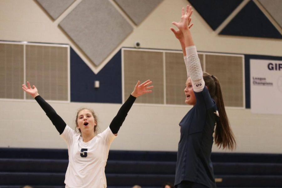 Smiling after scoring a point, junior Anna Judd celebrates with a teammate.