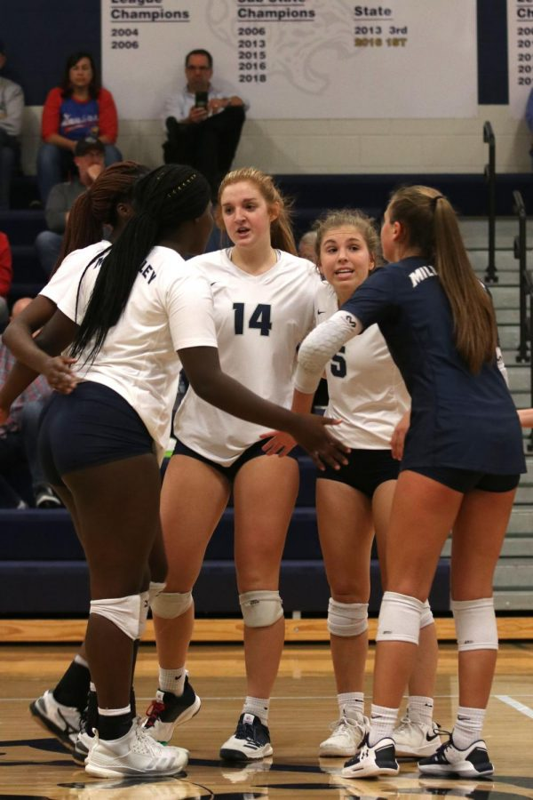 Gathering in a huddle on the court, junior Anna Judd communicates with the team.