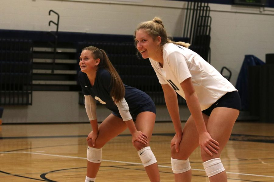 Awaiting the serve from the other team, sophomore Kate Roth and junior Jaden Ravnsborg smile at their fellow teammates on Thursday, Oct. 3.
