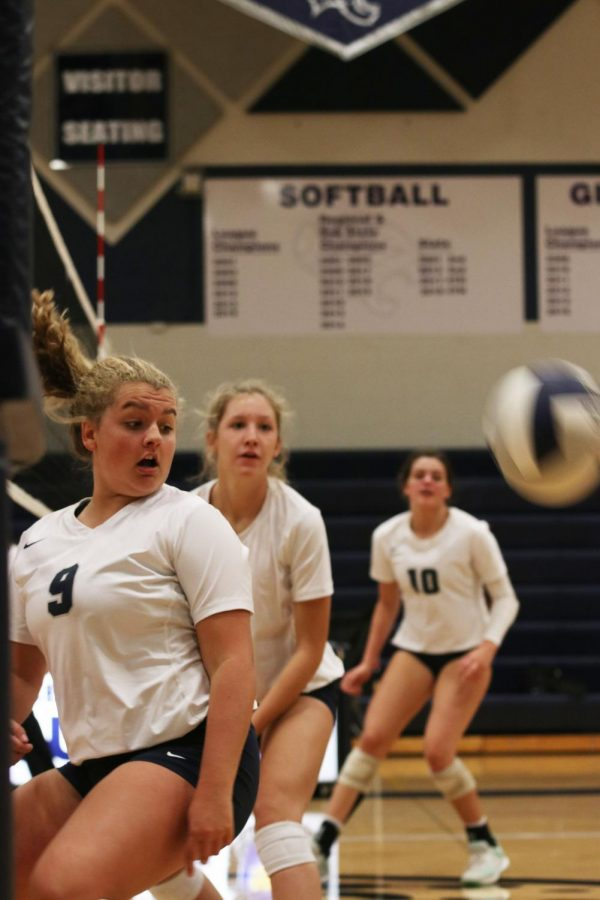 Watching the ball soar over the net, junior Landry Haydock turns her head to look behind her.