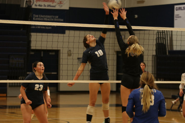 One hand raised, junior Molly Carr blocks the ball.