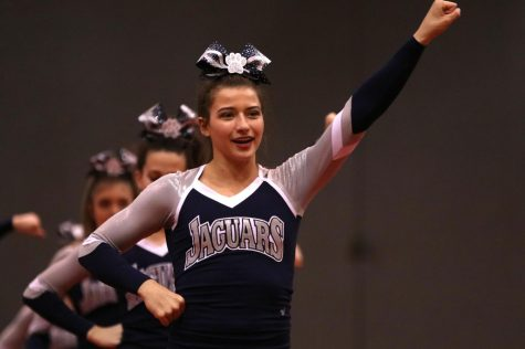 Finishing the crowd leading portion, senior Ellie Kerstetter holds her position. The cheer team received a two rating at their first competition of the season Saturday, Nov. 16.