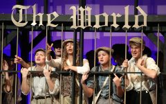 Reaching out, senior Annie Bogart and the rest of the Newsies want to be let out.