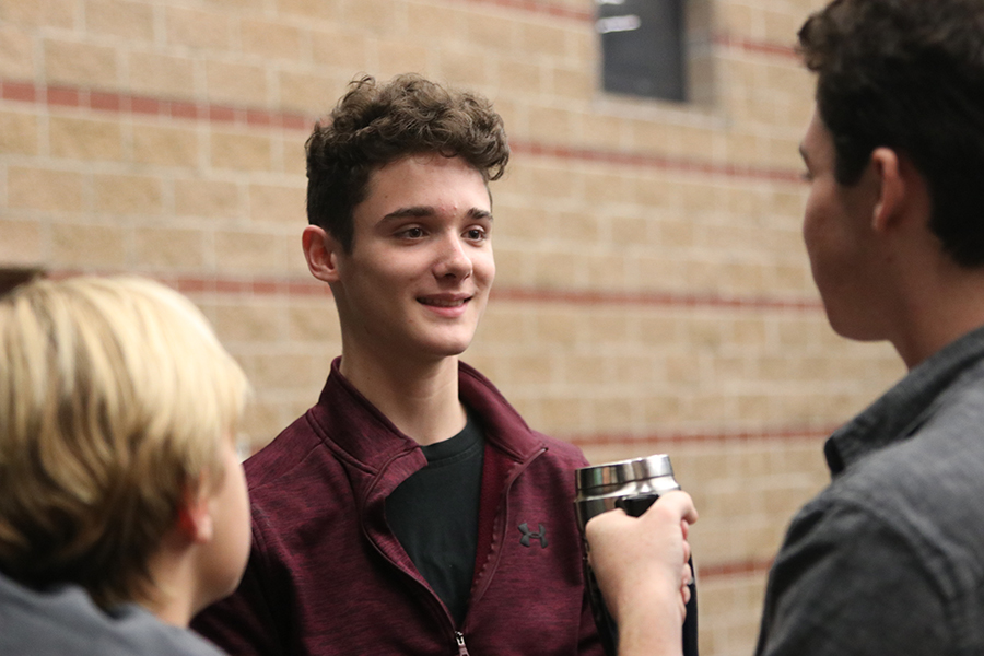 "Smiling at his friends, freshman Brayden Heath chats with his castmates before their musical rehearsal for ""Newsies""."