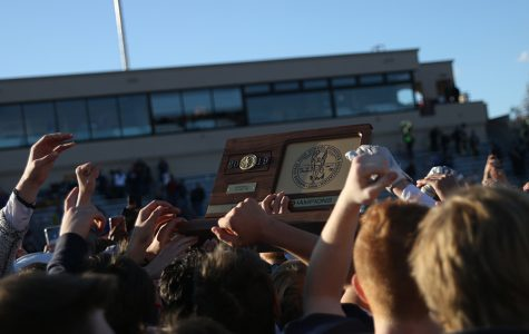 After the victory, everyone huddles around the State Trophy.