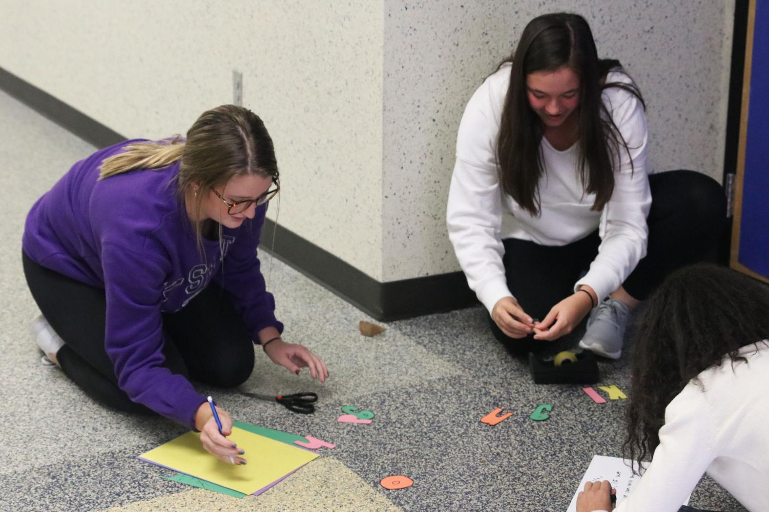 Cutting out letters, juniors Kenzie Harris and Ryleigh Reigle create their seminar door decorations. Throughout the past couple weeks, students participated in the annual Red Ribbon Week with this fun activity to express the effects of vaping and alcohol on teens.