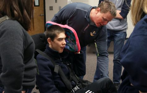 Dave Hayden explains the placement of Olathe West senior Ty Hayden's harness to the four Engineering Design and Development students on Friday, Nov.15. For their year-long project, they hope to create a modified seat belt that will help with transportation for people with special needs.