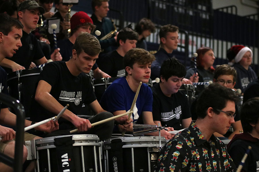 Focusing, the drumline performs a song.