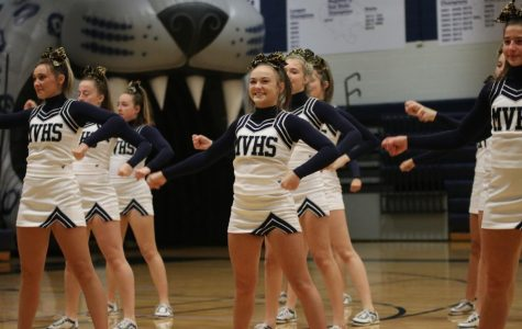 Smiling, senior Trinity Ouellette and the rest of the cheer team perform their first cheer of the pep rally Friday, Nov. 29.