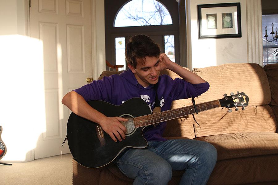 Preparing to play, sophomore Derik Bandad warms up his guitar