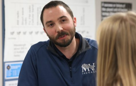 Listening intently, physics teacher Ryan Johnston speaks with a student.