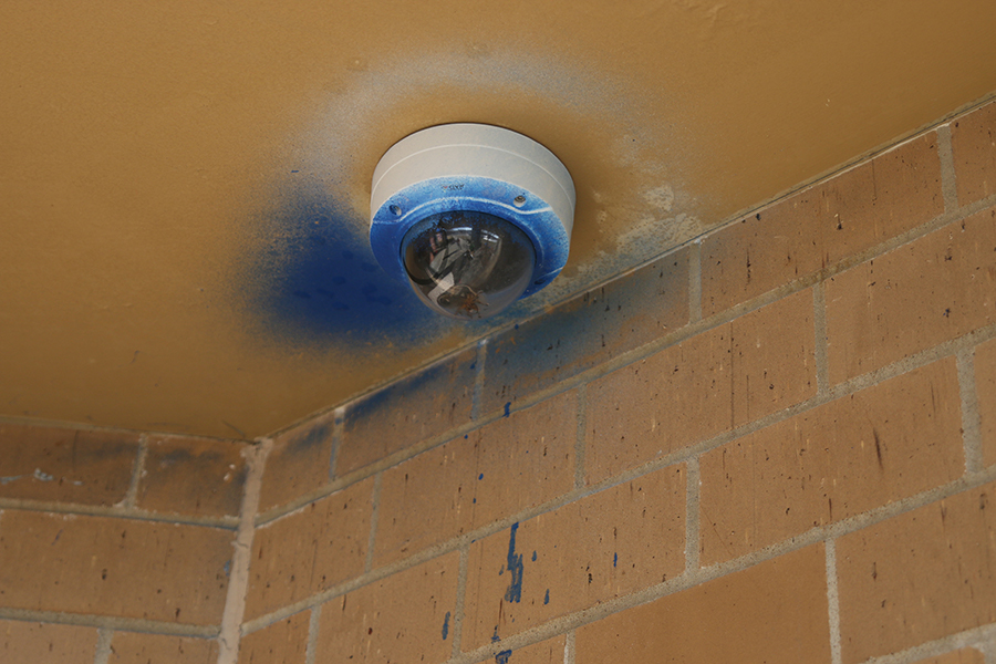 A security camera outside the media center remains covered in blue spray paint from the vandalism.