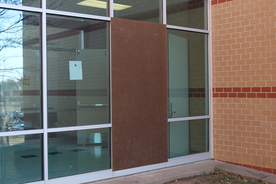 A board covers the window broken by vandals.