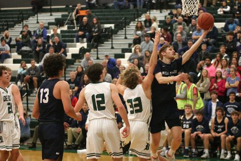 After getting past the defender, senior Braeden Wiltse goes up for a shot. The boys basketball team played in their first tournament of the season with their first competition game being against the De Soto Wildcats, where they defeated them with a final score of 47-42.