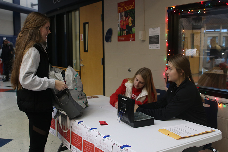 Buying a candy cane from sophomore Bridget Roy and junior Callie Shryock, junior Emily Feuerborn supports NEHS in their annual candy cane sale the week before finals.