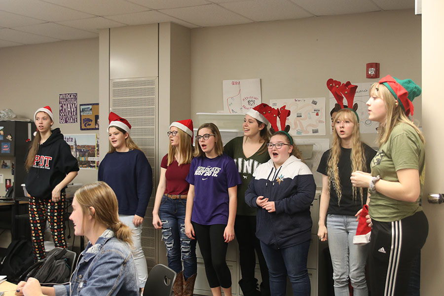 Choir members sing a Christmas carol while StuCo members collect money.