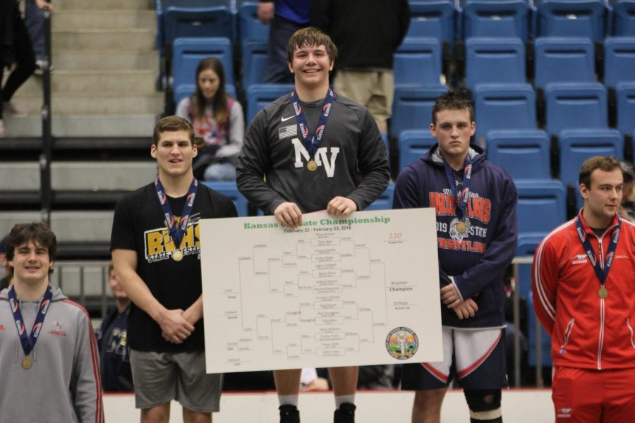 Junior Ethan Kremer poses with the winning bracket after winning the 220-pound weight class on Saturday, Feb. 23. Photo by Marah Shulda.