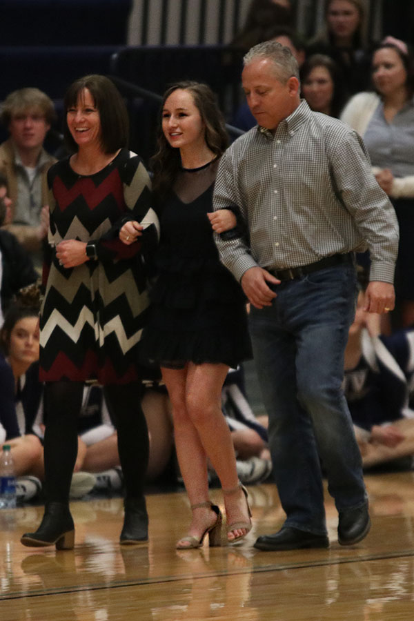 Smiling with her mom and dad beside her, candidate Rylee McElroy walks in front of the crowd.