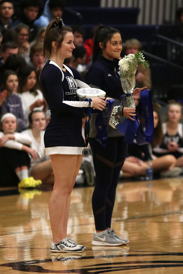 Seniors Kaylea Cummings and Ali Greenhalgh wait for the winning candidates to be announced while holding the crown, flowers and a sash to give to them.