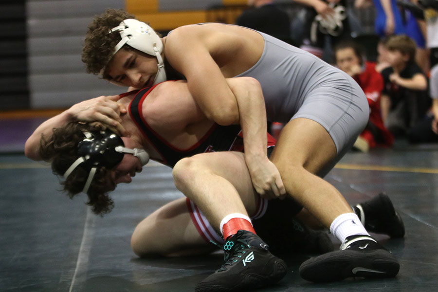 Holding his opponent down, senior Zach Keal tries to force him down on the mat.
