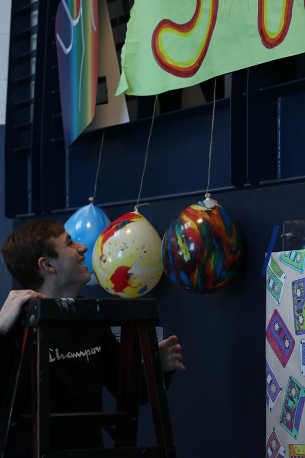 StuCo vice president Wyatt Lindsey helps move the balloons near the senior poster.