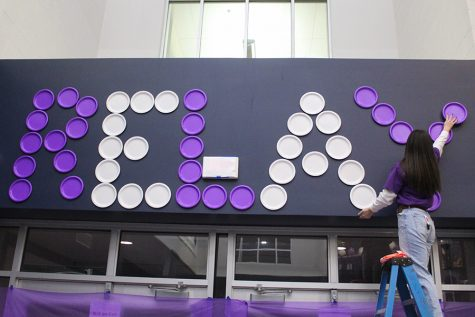 "Using plates, senior Lauren Johnson creates a huge display that says ""RELAY"" on one side of the schools entrance."