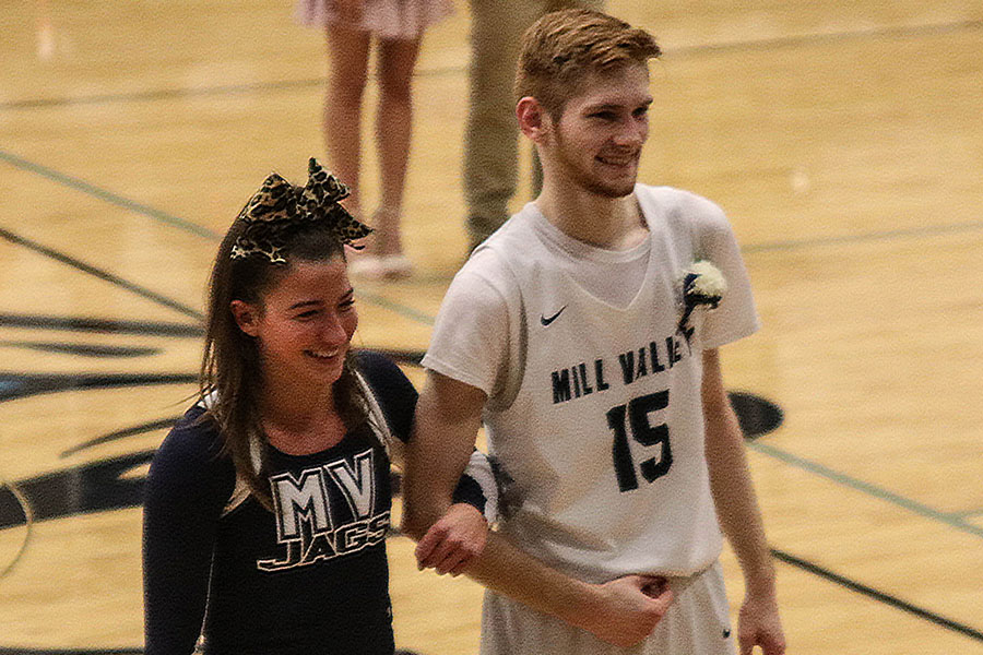 Homecoming king candidate Braeden Wiltse walks with senior Ellie Kerstetter, standing in for queen candidate Anna Paden, during the coronation at halftime of the boys varsity game Friday, Jan. 1.