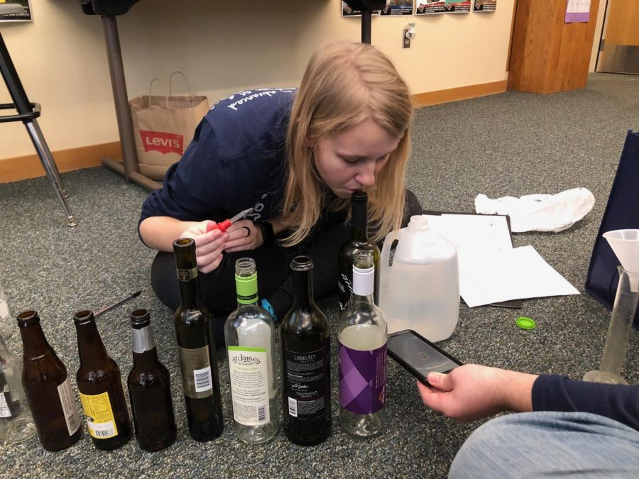 Prior to competing in Sounds of Music, senior Callie Roberts adjusts the pitch of each of the bottles by adding specific amounts of water and blowing into the bottle. The team of Roberts and junior Andrew Gawith made their project using different sizes of bottles and creating different notes by adjusting the water levels in each.