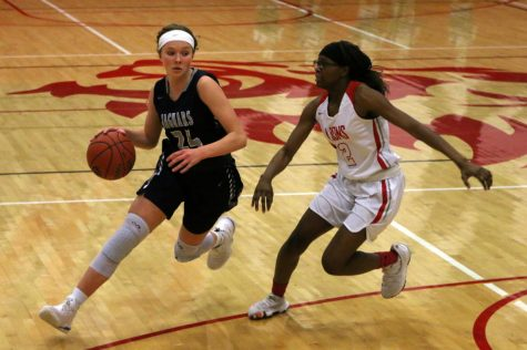 Dribbling the ball, sophomore Emree Zars runs past an opponent. The team fell to the Lansing Lions 52-24 at Lansing Tuesday, Jan. 22.
